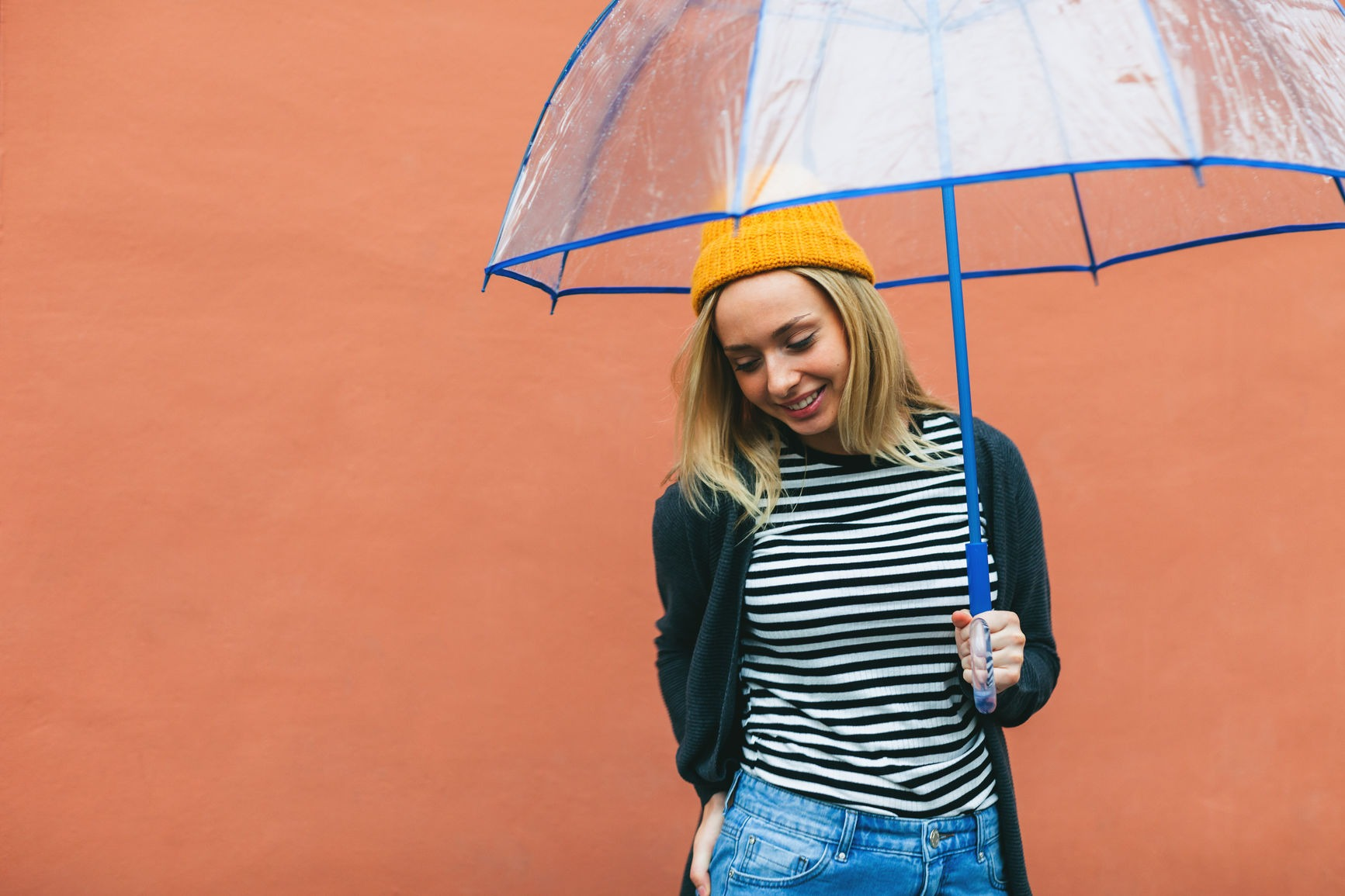 Blonde Woman Holding An Umbrella In Front Of An Orange Wall.